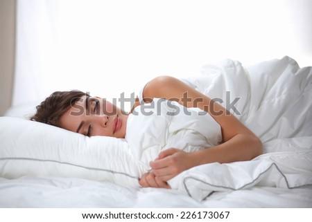 Beautiful girl sleeps in the bedroom, lying on bed, isolated #226173067