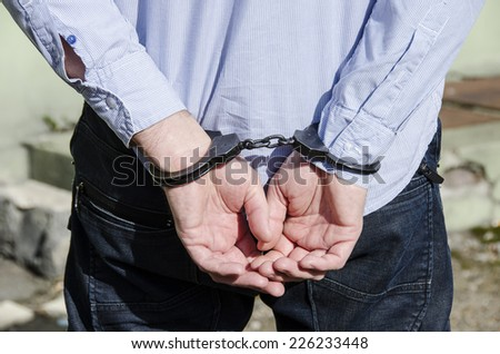 Photo of man in handcuffs.