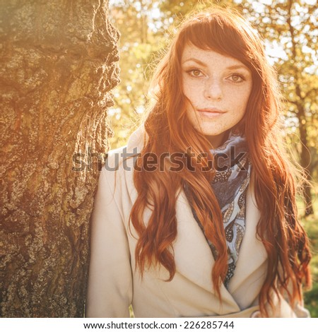 beautiful woman with freckle and red long hair in autumn park #226285744