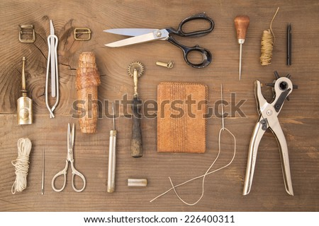 Leather craft tools on a wooden background Royalty-Free Stock Photo #226400311