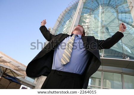 A business man celebrating success outside his office building #2264015