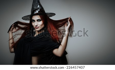 Halloween fantasy theme: redhead witch girl on gray background #226457407