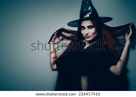 Halloween fantasy theme: redhead witch girl on gray background #226457416
