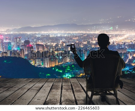 Silhouette of businessman sit on chair and hold a cigar and looking at the city in night. #226465603