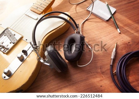 Guitar recording scene. An electric guitar, memo pad , and a professional grade headphones on a rustic or bare wooden table, with by-the-window type warm light coming in.