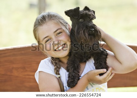 Portrait of a beautiful young girl holding her dog while enjoying a summer day #226554724
