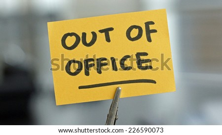 Out of office written on a card at the desk
