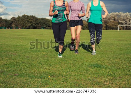 Three fit young women are running on the grass in a park #226747336