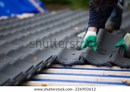 Hands of a man laying tiles on the roof while roofing a house near the city of Breda, Netherlands, Europe, in a traditional craftsman way #226903612