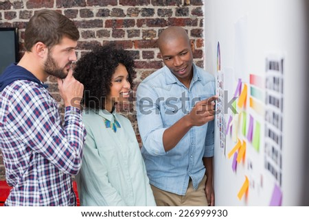 Creative business team looking at sticky notes on wall #226999930