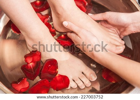 Closeup photo of female feet at spa salon on pedicure procedure. Female legs in water decoration flowers and getting massage