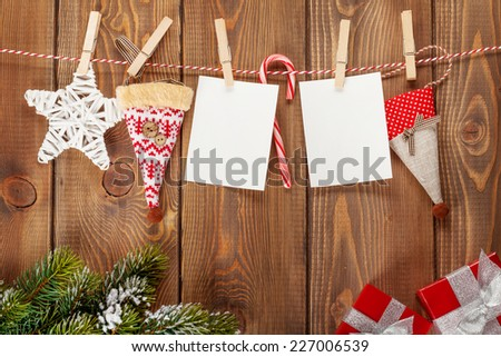 Snow fir tree, photo frames and christmas decor on rope over rustic wooden board with copy space