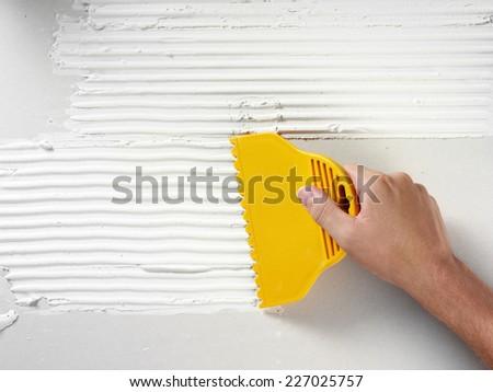 MAN TILING A WALL #227025757