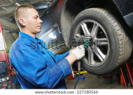 car mechanic screwing or unscrewing car wheel of lifted automobile by pneumatic wrench at repair service station #227180566
