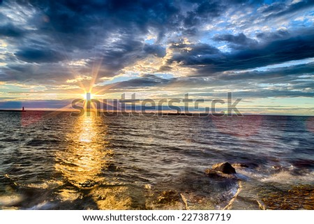 Sunset on the Mediterranean sea with red steel lookout on eyot and green top white lighthouse in the cloudy background near Porec in Croatia #227387719