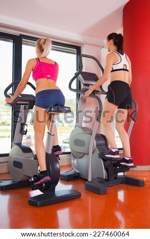 Woman exercising at the gym on a cross trainer #227460064
