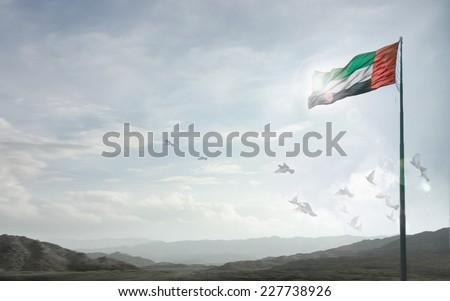 A massive flag of UAE flying against a horizon of Hajjar mountains, Fujeirah, UAE. Royalty-Free Stock Photo #227738926