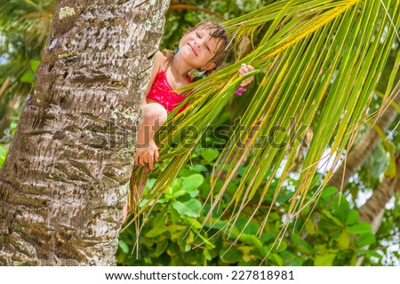 outdoor portrait of young happy child girl in tropical background with palm trees #227818981
