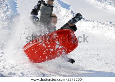 boy in the air while sledding fast down the hill with snow background #22782004