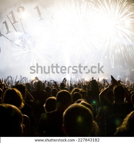 New Year concept - cheering crowd and fireworks #227843182