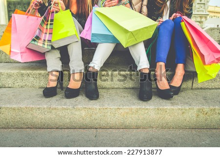 Women with high heels and shopping bags - Three girls sitting on stairs and chatting after buying presents #227913877
