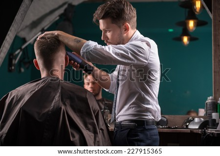 hairdresser  cuts    hair  with hair clipper on back of the head of handsome satisfied  client in  professional  hairdressing salon low angle #227915365