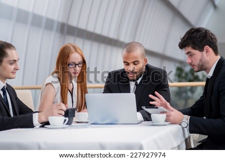 Business partners meeting with clients. Four smiling successful businessmen sitting at table in office while discussing their business doings. Young men dressed in formal wear #227927974