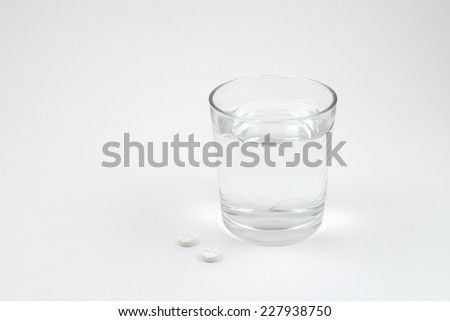 Glass with water and pills isolated on white background #227938750