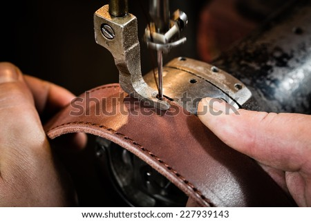 Sewing process of the leather belt. Man's hands behind sewing. Leather workshop. Royalty-Free Stock Photo #227939143
