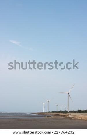 Wind turbines at seaside against blue sky #227964232