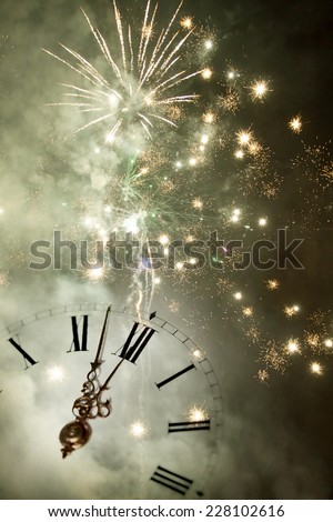 New Year's at midnight - Old clock with fireworks and holiday lights #228102616
