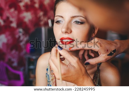 Young beautiful bride applying wedding make-up by professional make-up artist #228245995