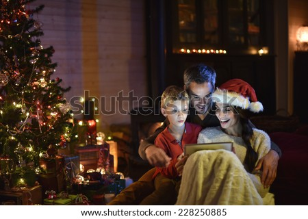 lovely family sharing a digital tablet near the wood stove on a winter evening, enjoying the warmth of Christmas in their living room, the young woman wears a hat of Santa Claus #228250885