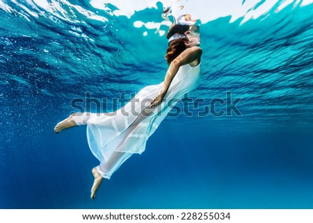 Nice girl emerges from the sea, swimming underwater, enjoying nice refreshing water, wearing long dress, summer vacation and travel concept  #228255034