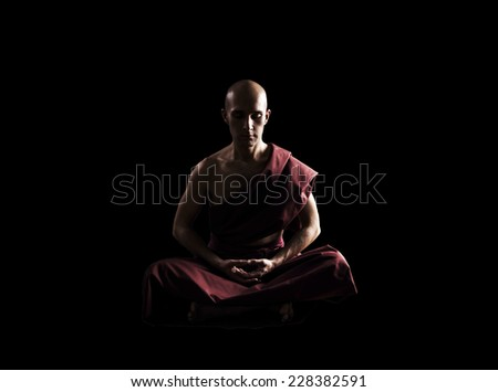 buddhist monk in meditation pose over black background #228382591