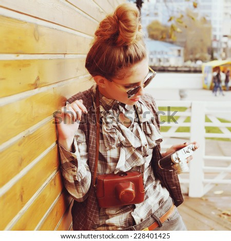 Outdoor lifestyle portrait of pretty funny hipster woman making photo. Retro photographer. Modern urban girl has fun with vintage photo camera, wooden background. Photo toned style Instagram filters.