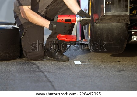 Race car being serviced with new slick tires by a mechanic during a race in the pit lane #228497995