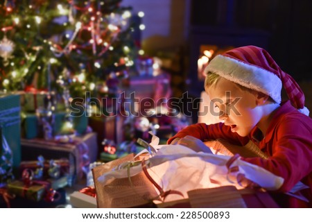 Lovely little boy with a santa claus hat opens a gift in front of the Christmas tree lit up, in the warm atmosphere of Christmas,  a wood stove in the background
