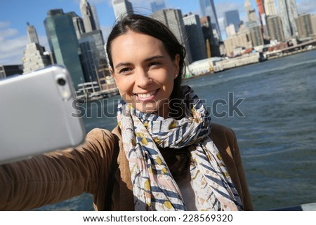 Brunette girl making selfy with Manhattan in background #228569320