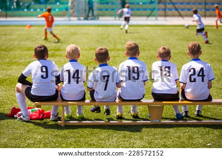 Football soccer match for children. Kids waiting on a bench. Royalty-Free Stock Photo #228572152