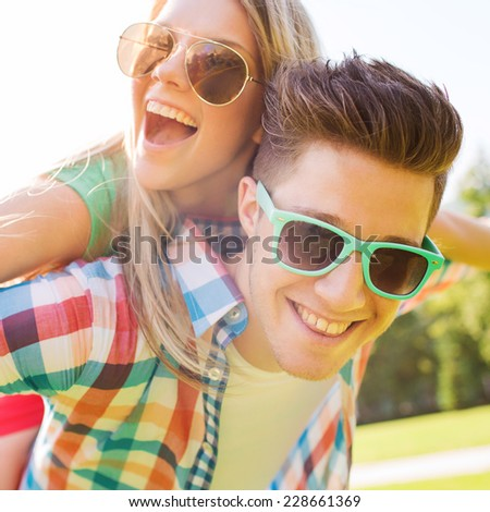 holidays, vacation, love and friendship concept - smiling teen couple in sunglasses having fun in summer park #228661369