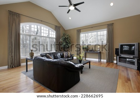 Family room with large picture window and brown walls