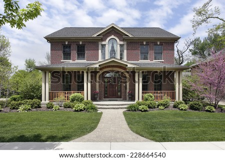 Brick home with white columns and arched entry #228664540
