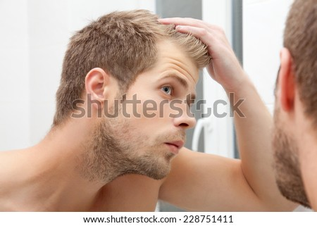 Handsome unshaven man looking into the mirror in bathroom Royalty-Free Stock Photo #228751411