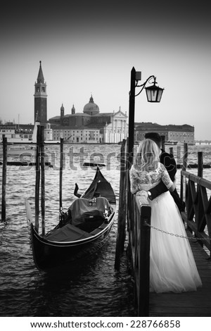 Romantic married couple in Romantic Italian city of Venice in black and white. Traditional Venetian wooden gondola and Roman Catholic church of San Giorgio Maggiore in the background. #228766858