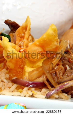 Chinese crab rangoon and Mongolian beef on friend rice in kitchen or restaurant setting. #22880158