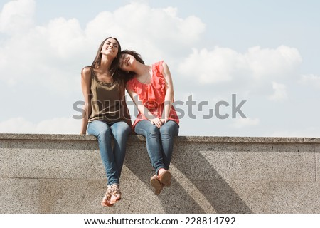 Best friends. Emotional portraits of beautiful brunettes on background of clouds. Pleasant emotions, happy mood. Female friendship. City street