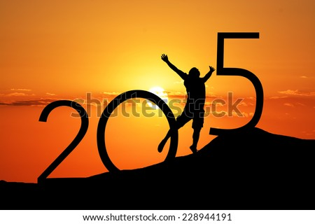 Silhouette person jumping over 2015 on the hill at sunset Royalty-Free Stock Photo #228944191