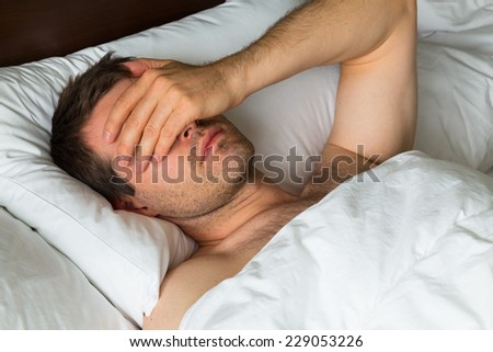 A man covering his eyes with his hand as he doesn't want to take up #229053226