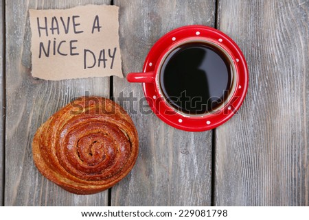 Composition of coffee, fresh bun and paper card on wooden background